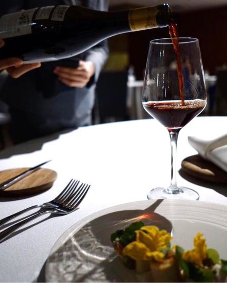 sommelier pouring burgundy into glass restaurant